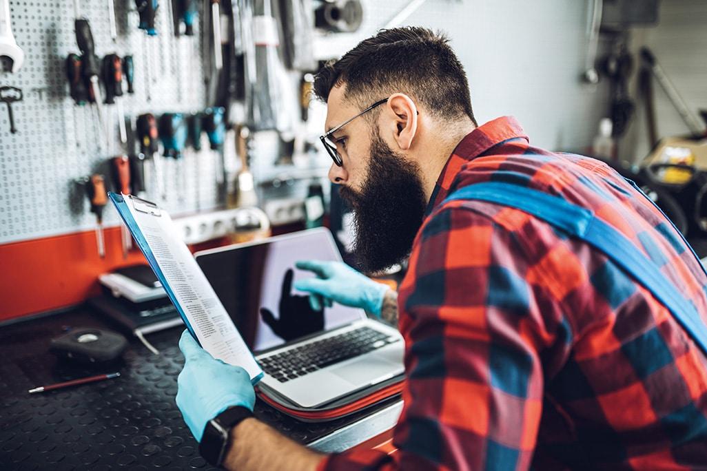 Technician loads laptop with vehicle diagnostics